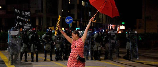 Une manifestante se tient avec son parapluie devant des policiers à Hongkong le 1er octobre.