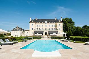 L'hotel-restaurant chateau de Saulon-La-Rue en Bourgogne, cote piscine, ouvre grand sur un parc plante d'arbres centenaires.