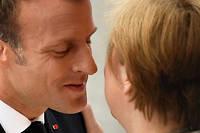 <p>Emmanuel Macron fait la bise à Angela Merkel le 14 juillet 2019.</p>