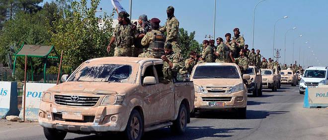 Des membres de l'Armee nationale syrienne, suppletifs des forces turques, partent pour Ras al-Ain au nord de la Syrie depuis la ville frontaliere de Ceylanpinat le 10 octobre.