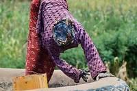 <p>Une femme reprend le toit d'une maison. Chaque année, vers le mois de mai, juste avant la saison des pluies, les femmes procèdent collectivement à la décoration murale de leur case.</p>