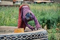 Une femme reprend le toit d'une maison. Chaque année, vers le mois de mai, juste avant la saison des pluies, les femmes procèdent collectivement à la décoration murale de leur case.