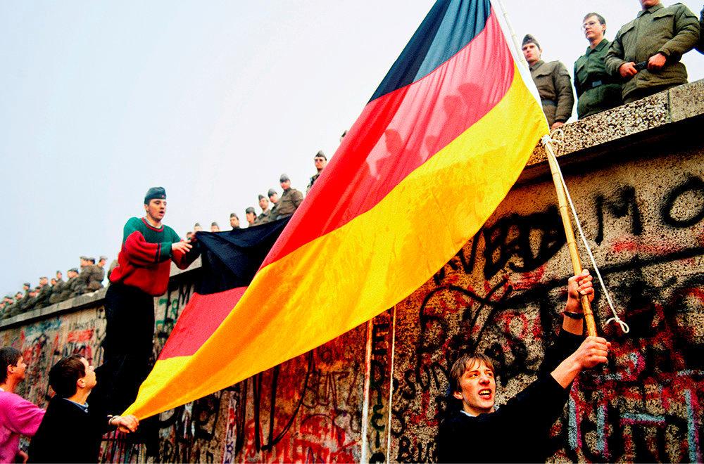 Liberté. Au matin du10novembre, unjeune Allemand del'Ouest nargue lesgardes-frontières est-allemands, juchés sur le Mur, en déployant ledrapeau de la République fédérale d'Allemagne. C'est la fin de la guerre froide et les prémices de la réunification allemande.