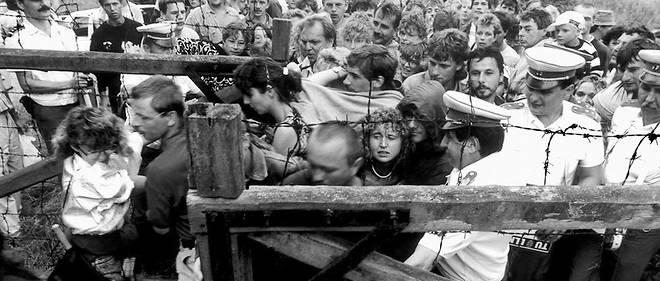 Des citoyens d'Allemagne de l'Est, qui se sont précipités au pique-nique de Sopron, le 19août 1989, à la frontière austro-hongroise, forcent la frontière entre l'Est et l'Ouest, sous le regard passif de la police des frontières hongroise.