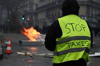 Un manifestant avec écrit stop taxes sur son gilet jaune. Les Gilets jaunes s'insurgent dans Paris pour l'épisode 3.
