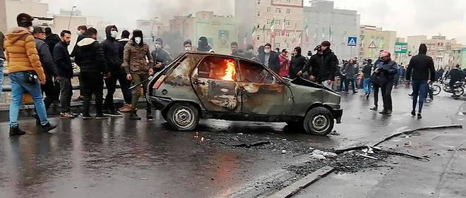 Des manifestants iraniens sont rassemblés autour d'une voiture en feu pour protester contre la hausse soudaine du prix de l'essence, le 16 novembre 2019 à Téhéran.