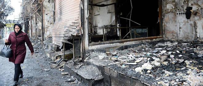 Une habitante de la ville de Karaj, près de Téhéran, marche devant les locaux d'une banque incendiée, le 20 novembre 2019.