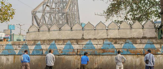Des hommes urinent dans la rue à Calcutta.