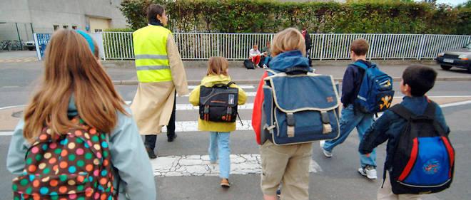 Une mère de famille vêtue d'un gilet accompagne, le 30 septembre 2005, des enfants qui empruntent le Pédibuspour se rendre à leur école du Clos Herbert à Caen.