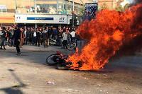 Des manifestants devant une moto brûlée à Isfahan en Iran le 16 novembre 2019.