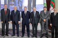 Les cinq candidats à la présidentielle du 12 décembre avec à gauche l'ancien ministre de la Culture Azzedine Mihoubi, lesanciens Premiers ministres Abdelmajid Tebboune (2 e  en partant de la gauche) et Ali Benflis (3 e  à droite), le chef du parti du mouvement Mostakbal Abdelaziz Belaid (2 e  à droite), et l'ancien ministre du Tourisme Abdelkader Bengrina (3 e  droite) aux côtés du chef de l'Autorité nationale pour les élections indépendantes (ANIE) Mohamed Charfi (R) lors d'une conférence de presse après avoir signé une charte d'éthique dans la capitalele 16 novembre 2019.