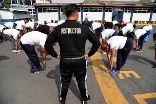 Dégoulinants de sueur sous le soleil de Mexico, un rictus de souffrance déformant leurs visages, des policiers bien en chair enchaînent pompes, étirements et abdominaux.