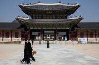 Deux femmes portant des masques de protection se promenent devant le palais de Gyeongbok a Seoul.