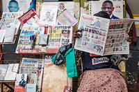 A man reads newspapers reporting about Uganda's upcoming elections at a kiosk in Kampala, Uganda, on January 4, 2021. - Uganda gears up for presidential elections which is scheduled to take place on January 14, 2021, as President Yoweri Museveni seeks another term to continue his 35-year rule. (Photo by SUMY SADURNI / AFP)