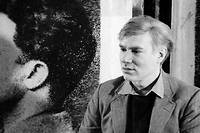 Portrait de l'artiste americain Andy Warhol (1928-1987) chef de file du mouvement Pop Art, posant pres d'une de ses serigraphies dans son atelier The Factory a New York.