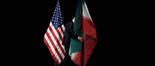 An official hoists Iranian and American flags on stage after the conclusion of the Iranian nuclear deal on July 14, 2015 in Vienna, Austria.